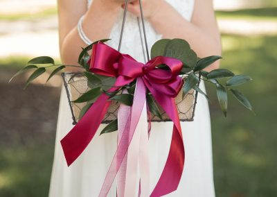 Flower girl carrying a basket with burgundy ribbons and florals